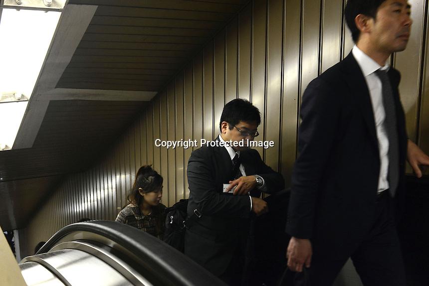 Businessmen on an escalator on the Tokyo underground, Tokyo, Japan.<br /> April-2014