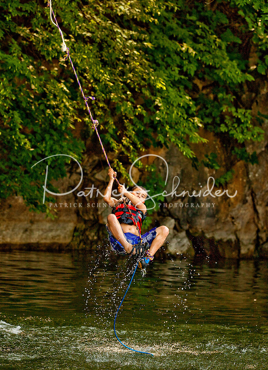 Visitors to Watauga Lake, Tennessee, swing from a rope into the pristine lake. Lake Watauga, located between Boone, NC, and Elizabethton, TN, is surrounded by Cherokee National Forest and is largely undeveloped.