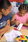 Preschool female parent volunteer working with child