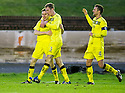Queen of the South's Paul Burns (7) celebrates with Kevin Holt (3) and Stephen McKenna (4) after he scores their first goal.
