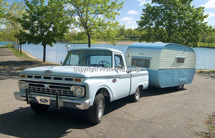 Light blue 1966 Ford F100 pulling a two-toned blue and white 1957 Sportcraft vintage travel tailer.