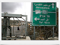 A Palestinian man prays behind a a massive metal gate block at the the exit of the Palestinian village of al-Tira  to Road No. 443. Road 443 is one of the main throughways of the West Bank. Its overall length is 25.5 KM, 14 out of which run through the heart of the West Bank. .With the break of the second Intifada at the end of 2000, Israel had severely restricted Palestinian movement on road 443, which was their main road from the Beit Sira, Saffa, Beit Liqiya, Kharbatha al-Misbah, Beit Ur al-Tahata, Beit Ur al-Foqqa and al-Tira villages to Ramallah. These restrictions were harshened in 2002, when Palestinian movement was completely prohibited. In recent years all entries and exits from the road to the area's villages were blocked with gates and concrete slabs. Photo by Quique Kierszenbaum.