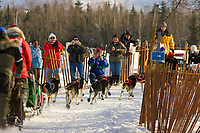 Spectators take photos and cheer on Andrew Angstman as he travels along the bike trail during ceremonial start of Iditarod Alaska