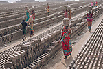 Labourers carry patterned bricks through fields of the clay blocks.  More than 100 workers mould bricks from clay before they are left to dry for three days and then burned. <br /> <br /> Each brick weighs around 6lbs with workers transporting up to 12 bricks on their heads at a time.   The brick fields stretch for almost a kilometre in the city of Narayanganj, in central Bangladesh.   SEE OUR COPY FOR DETAILS.<br /> <br /> Please byline: Ratul Dhar/Solent News<br /> <br /> © Ratul Dhar/Solent News & Photo Agency<br /> UK +44 (0) 2380 458800