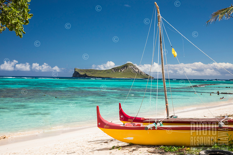 A brightly colored outrigger canoe lies in the foreground of this Waimanalo Beach scene in Windward O'ahu. Residents and tourists alike explore the reef of Waimanalo Bay, with Rabbit Island in the distance.
