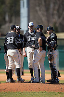 LIU-Brooklyn Blackbirds head coach Alex Trezza has a meeting on the mound with his team during the game against the High Point Panthers at Willard Stadium on March 8, 2015 in High Point, North Carolina.  The Panthers defeated the Blackbirds 9-0.  (Brian Westerholt/Four Seam Images)