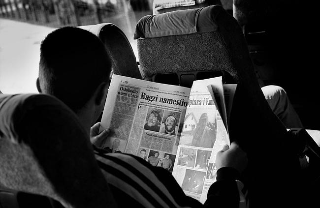 SERBIA, Belgrade-Sarajevo Road, 03/2003..We travell during the state of emergency few days after the murder of Zoran Djindjic. In the bus, six soldiers go back home, reading the newspapers (arrests, new murders). .SERBIE, Route Belgrade-Sarajevo, 03/2003..Photo prise depuis le bus qui relie Belgrade à Sarajevo. Nous voyageons pendant la période d'état d'urgence, quelques jours après le meutre du premier ministre Zoran Djindjic. Dans le bus, six soldats rentrent à la maison, lisant le journal (arrestations, nouveaux meurtres). © Bruno Cogez .