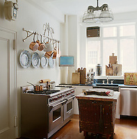In the kitchen, in front of the stainless steel Wolf range, a butcher's block has been created from a large antique wicker basket topped with a contemporary wooden surface
