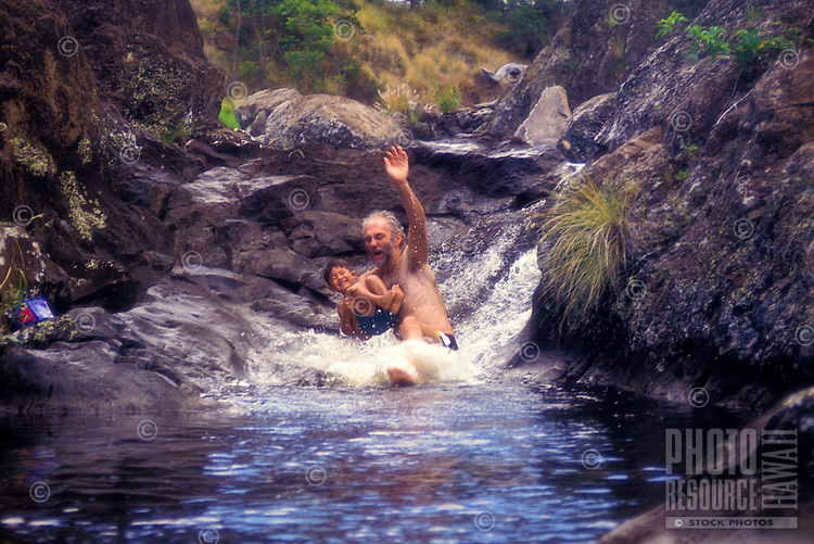 A father and son playing in a waterfall, waimea