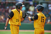 Jacksonville Suns outfielder Matt Juengel (15) fist bumps Terrence Dayleg (16) after hitting a home run during the 20th Annual Rickwood Classic Game against the Birmingham Barons on May 27, 2015 at Rickwood Field in Birmingham, Alabama.  Jacksonville defeated Birmingham by the score of 8-2 at the countries oldest ballpark, Rickwood opened in 1910 and has been most notably the home of the Birmingham Barons of the Southern League and Birmingham Black Barons of the Negro League.  (Mike Janes/Four Seam Images)