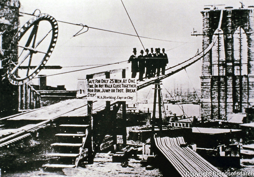Historical photograph of men on catwalk during Brooklyn Bridge construction. Note the caution sign.