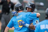 Gleyber Torres (11) of the Myrtle Beach Pelicans gets a hug from teammate Ian Happ (5) after hitting a solo home run in the top of the first inning against the Winston-Salem Dash at BB&T Ballpark on April 19, 2016 in Winston-Salem, North Carolina.  The Dash defeated the Pelicans 6-5.  (Brian Westerholt/Four Seam Images)