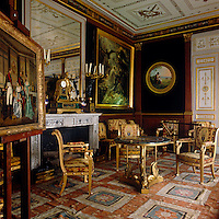 The Salon at Malmaison features white and gold decorations. The chairs were designed by Jacob Desmalter and the large painting is by Anne-Louis Girodet and honours the heroes who died for France