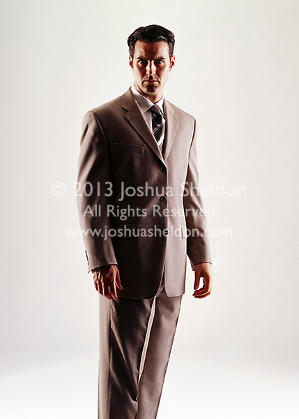 Caucasian looking man wearing a tan suit looking at camera