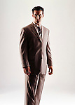 Caucasian looking man wearing a tan suit looking at camera