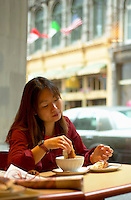 June 16 , 2002, Montreal, Quebec, Canada<br /> <br /> A Japanese tourist enjoy the French culture of Montreal<br /> by eating  a chololate croissant and caffe latte (coffee with milk) in a Old Montreal  coffee  shop, June 16 , 2002.<br /> <br /> Model released for editorial use only.<br /> Any commercial / advertising use is subject to the coffee shop owner approval<br /> <br /> Mandatory Credit: Photo by Pierre Roussel- Images Distribution. (©) Copyright 2002 by Pierre Roussel <br /> <br /> NOTE Nikon D-1 jpeg opened with Qimage icc profile, saved in Adobe 1998 RGB. Original size - uncropped TIFF file available on request.