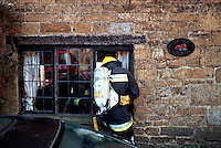 Firefighters, in breathing apparatus, are preparing to enter a thatched house on fire through a ground floor window. This image may only be used to portray the subject in a positive manner..©shoutpictures.com..john@shoutpictures.com