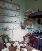 A large painted dresser in the kitchen holds the green and white porcelain dinner service and a place for breakfast is set at the kitchen table