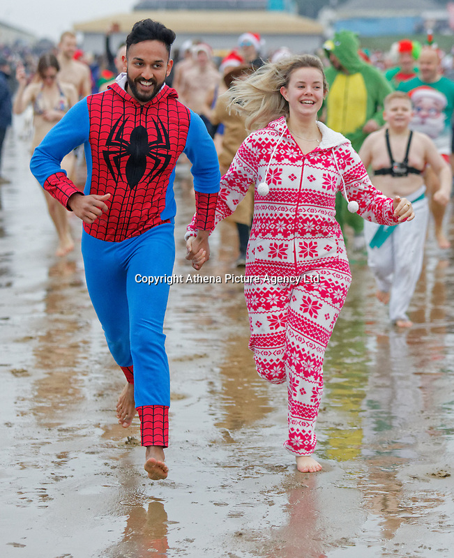 Pictured: A man dressed as Spiderman and a young woman in a festive onesie, run to the sea. Tuesday 25 December 2018<br /> Re: Hundreds of people take part in this year's Porthcawl Christmas Swim in south Wales, UK.