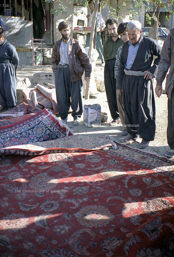 Irak 2000.Vente de tapis dans une rue d'Halabja.Iraq 2000. Halabja:Selling carpets on the pavement