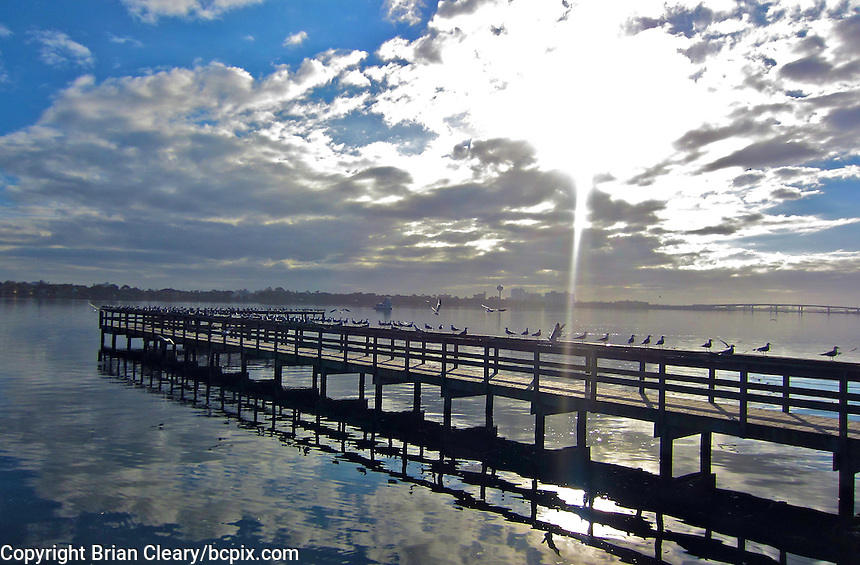 A dock on the Halifax River under early morning clouds, Holly Hill, Florida.  (Photo by Brian Cleary/www.bcpix.com)