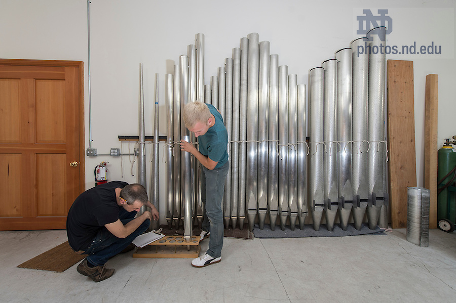 Erik McLeod (left) and Zane Boothby measure the foot of a bass pipe.