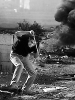 Palestinian ducking as Isreali soldiers fire towards him.  Ramallah. Palestine.