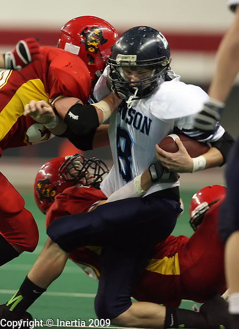 VERMILLION, SD - NOVEMBER 13: Andrew Gross #8 of Hanson is brought down by Jeff Bertus #26, left, and Jon Vilhauer #17 of Avon in the fourth quarter of the South Dakota Class 9A Championship game Friday, November 13, 2009 at the DakotaDome in Vermillion, SD. (Photo by Dave Eggen/Inertia)