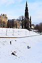 Edinburgh, UK. 29.12.2020. A family enjoys the first snowfall of the first Covid Winter, in front of the Scott Memorial, Princes Street Gardens, Edinburgh. Edinburgh has been placed in Tier 4 restrictions due to the Covid-19 pandemic. Photograph © Jane Hobson.