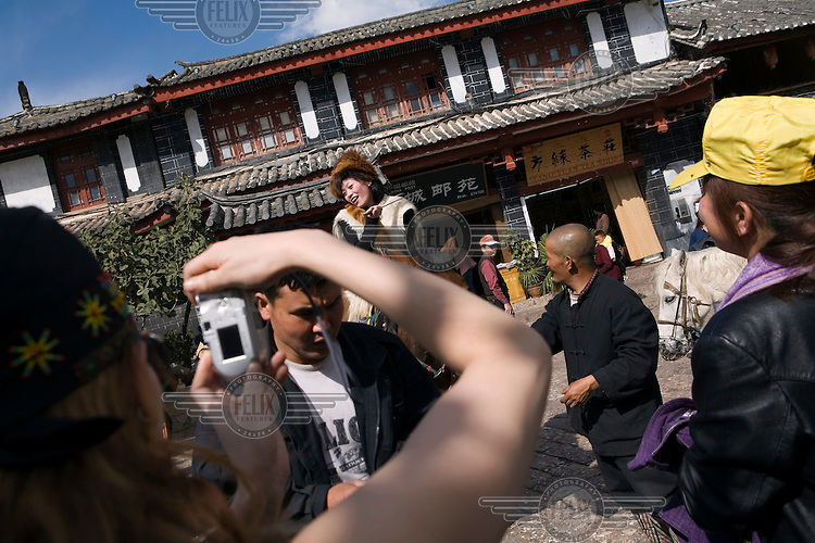 Tourists take photographs of Nakhi (Naxi) tour guides in the old city of Lijiang, a centre of Nakhi culture which is a UNESCO World Heritage Site.