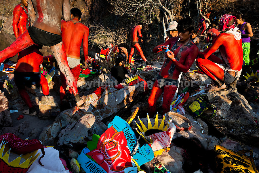 """Cora Indian boys, painting each other their bodies in red color, prepare themselves for the spiritual celebration of Semana Santa (Holy Week) in Jesús María, Nayarit, Mexico, 22 April 2011. The annual week-long Easter festivity (called """"La Judea""""), performed in the rugged mountain country of Sierra del Nayar, merges indigenous tradition (agricultural cycle and the regeneration of life worshipping) and animistic beliefs with the Christian dogma. Each year in the spring, the Cora villages are taken over by hundreds of wildly running men. Painted all over their semi-naked bodies, fighting ritual battles with wooden swords and dancing crazily, they perform demons (the evil) that metaphorically chase Jesus Christ, kill him, but finally fail due to his resurrection. La Judea, the Holy Week sacred spectacle, represents the most truthful expression of the Coras' culture, religiosity and identity."""
