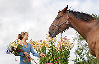 BNPS.co.uk (01202 558833)<br /> Picture: ZacharyCulpin/BNPS<br /> <br /> Horse and flower power...<br /> <br /> Kate White-Hamilton cuts huge Tree Lilies at her flower plot inWest Chelborough in Dorset in preparationforthe Flower Farmers' Big Weekend as Barney the horse looks on <br /> <br /> Flower farmers across the UK invited the public onto their plots for the third successive year of the Flower Farmers' Big Weekend. The weekendoffered flower-lovers the chance to meet and learn from the local, growers of seasonal, scented British cut flowers on their allotments, cutting gardens, walled gardens and farmland. Thenationwide open flower farm festival staged by growers' association.