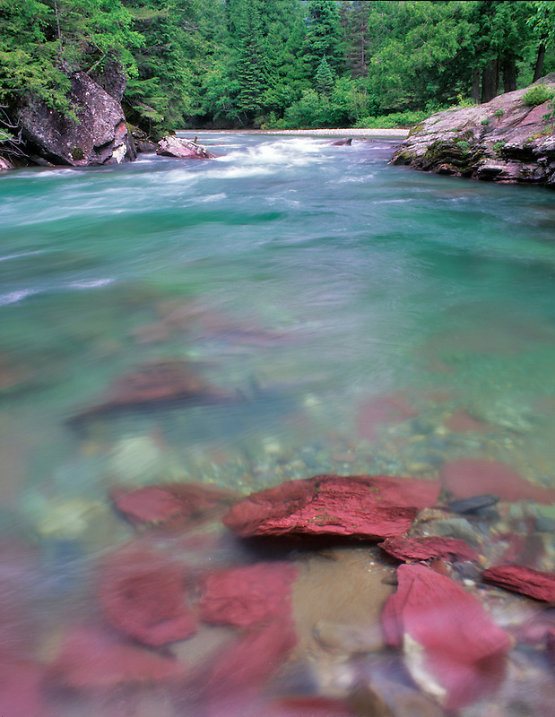 Red rock and green waters of McDonald Creek. Glacier National Park, Montana.