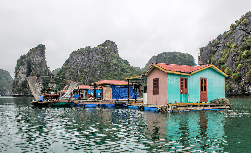 """A fishing village sits on the water in Vietnam's beautiful Ha Long Bay, which contains over 1,900 limestone """"karst"""" islands projecting from the sea."""