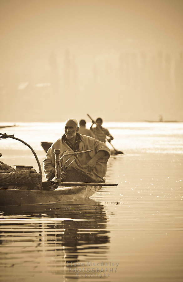 Muslim man with hooka on a Shikara, or gondola boat, on Dal Lake, Srinagar, Kashmir, India.