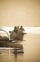 Muslim man with hooka on a Shikara, or gondola boat, on Dal Lake, Srinagar, Kashmir, India.