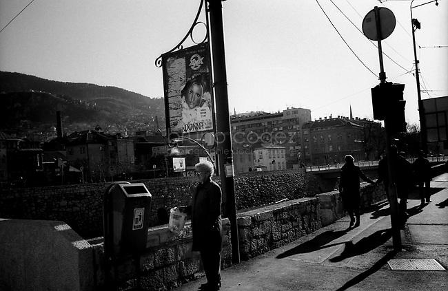 BOSNIA-HERZEGOVINA, Sarajevo, March 2003..10 years after the end of the war, I came for the first time in Sarajevo. I have in mind the images of the besieged city. The daily death, the impotence and the guilty inaction of the international community, the sad spectacle of a war in Europe. 10 years later, I walk the streets obsessed with the scars of war..Street scene on the banks of Miljacka river..BOSNIE-HERZEGOVINE, Sarajevo, Mars 2003..10 ans après la fin de la guerre, j'arrive pour la première fois à Sarajevo. J'ai encore en tête les images de la ville assiégée. La mort quotidienne, l'impuissance voire l'inaction coupable de la communauté internationale, le spectacle désolant d'une guerre en Europe. 10 après, je déambule dans les rues obsédé par les stigmates de la guerre..Scène de rue sur les rives de la rivière Miljacka..© Bruno Cogez