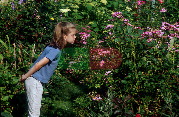 young girl in garden smelling flowers