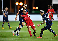 LAKE BUENA VISTA, FL - JULY 26: Nick DeLeon of Toronto FC passes the ball as James Sands of New York City FC and Valentín Castellanos of New York City FC look on during a game between New York City FC and Toronto FC at ESPN Wide World of Sports on July 26, 2020 in Lake Buena Vista, Florida.