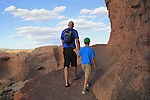 Father and son walking in Arches National Park, Moab, Utah, USA. .  John offers private photo tours in Arches National Park and throughout Utah and Colorado. Year-round.