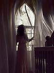 Woman in a long dress standing by a window with flying in the wind curtains in a dark house lit by dim sunlight Image © MaximImages, License at https://www.maximimages.com