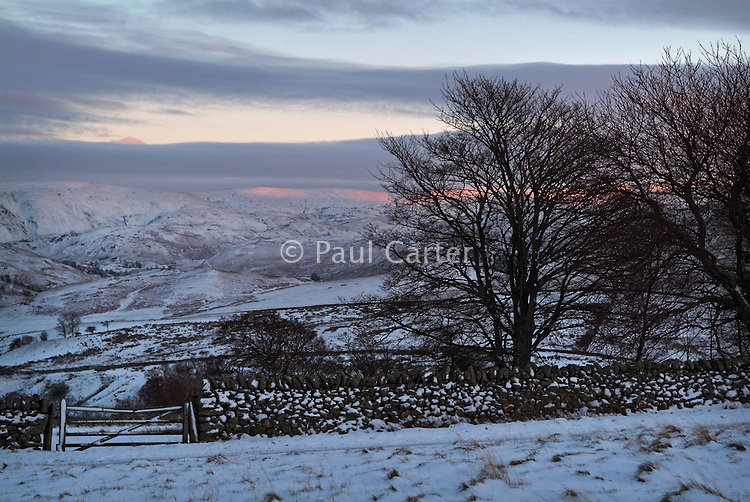 View over looking snow covered fields and hills, to the sunlight of sunset hitting the highest land.