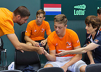Switserland, Genève, September 16, 2015, Tennis,   Davis Cup, Switserland-Netherlands, Practise Dutch team, team docor Babette Pluim and fysio Edwin Visser treating Tim van Rijthoven for a blister in the background Tallon Griekspoor<br /> Photo: Tennisimages/Henk Koster