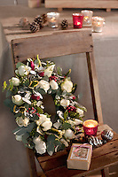 A floral wreath is propped against the back of a rustic chair with a small Christmas gift and a tealight