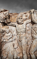 Detail of a Roman Sebasteion relief sculpture of Zeus and Prometheus, Aphrodisias Museum, Aphrodisias, Turkey.   Against a grey background.<br /> <br /> Prometheus is screaming in pain. Zeus had given him a terrible punishment for giving fire to man: he was tied to the Caucasus mountains and had his liver picked out daily by an eagle. Herakles shot the eagle and is undoing the first manacle. He wears his trade mark lion-skin and thrown his club to one side. A small mountain nymph, holding a throwing stick appears amongst the rocks.