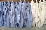 row of lab coats hanging on wall hooks