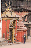 Bhaktapur, Nepal.   Man Looking at the  Golden Gate to the Royal Palace, beside the Palace of Fifty-five Windows, Durbar Square.  The gate survived the April 2015 earthquake with only minor damage.