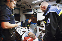 Switzerland. Canton Ticino. Lugano. A senior woman is brought by ambulance to hospital for medical examinations. The elderly man is suffering from a stroke. The emergency doctor Daniele Speciale (L) is working with two paramedics. They all work for theCroce Verde Lugano. They wear blue uniforms and medical gloves. The man (R) is a professional certified nurse, the woman (C) is a volunteer specifically trained in emergency rescue. A monitor controls the patient's vital functions, such as electrocardiogram, blood pressure's measurement, respiratory rate and pulse oximetry (oxygen saturation). On the aged woman's arm, an intravenous infusion with saline solution is fixed. TheCroce Verde Lugano is a private organization which ensure health safety by addressing different emergencies services and rescue services. Volunteering is generally considered an altruistic activity where an individual provides services for no financial or social gain to benefit another person, group or organization. Volunteering is also renowned for skill development and is often intended to promote goodness or to improve human quality of life. Medical gloves are made of different polymers including latex, nitrile rubber, polyvinyl chloride and neoprene. 13.01.2018 © 2018 Didier Ruef