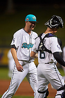 Salt River Rafters relief pitcher Ashton Goudeau (17) and catcher Brian Serven (6), both of the Colorado Rockies organization, laugh as they walk off the field between innings of an Arizona Fall League game against the Mesa Solar Sox on September 19, 2019 at Salt River Fields at Talking Stick in Scottsdale, Arizona. Salt River defeated Mesa 4-1. (Zachary Lucy/Four Seam Images)