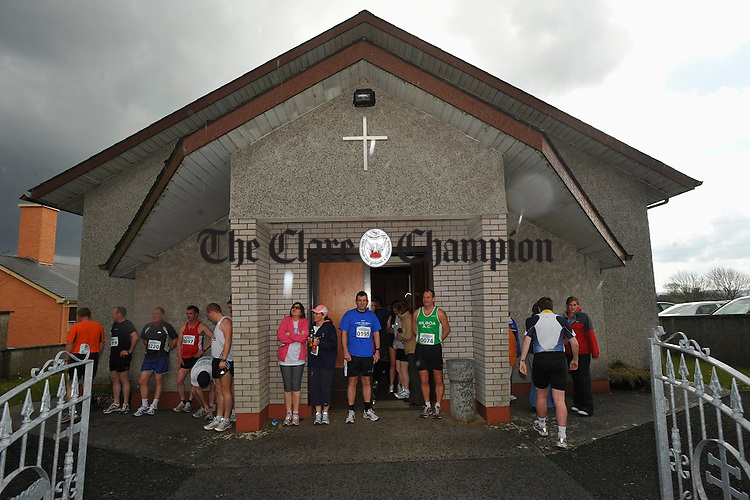 Athletes and supporters take refuge from the pouring rain  at the Sonny Murphy memorial 10k road race in Kilnaboy. Photograph by John Kelly.